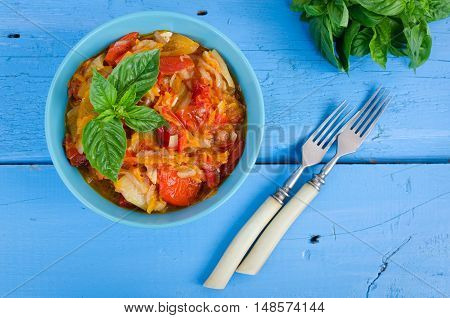 Italian peperonata: roasted bell pepper with basil in a bowl on blue wooden background. Pepper lecho stew ragout. Peperonata - traditional dish of italian cuisine. Italian cuisine concept. Top view.