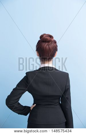 business woman arms akimbo and back to you with isolated on blue background asian