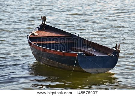 Anchored old rowboat and its reflection in the lake