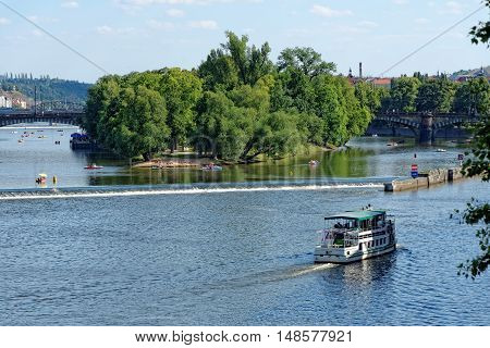 View of the Vltava river and Strelecky island with cruise tour boats from the Charles Bridge. The Charles Bridge is a famous historic bridge that crosses the Vltava river in Prague Czech Republic.