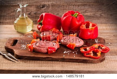 Raw sausage and bel pepper on wooden table.