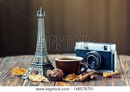 Love Autumn Paris! vintage camera Eiffel tower coffee cup chocolate autumn leaves cinnamon sticks on wooden table St Valentine's Day concept Nostalgic holidays background card with place for your text