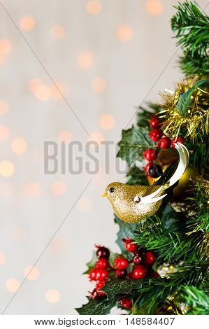 Festive Christmas close up of tree decorated with gold glitter robin tinsel and holly berries. Bokeh background copy space. Vertical.