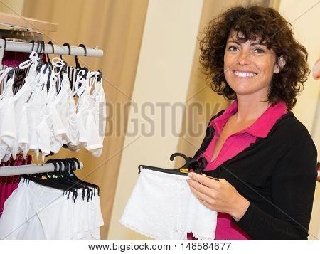 Joyful Female Shopper Holding A Hanger With Panties At Clothing Shop
