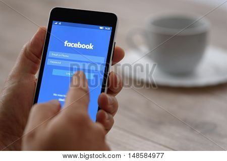 Krynica Poland - September 23 2016: Smartphone in the hand when logging into Facebook applications. Facebook is largest and most popular social networking site in the world.