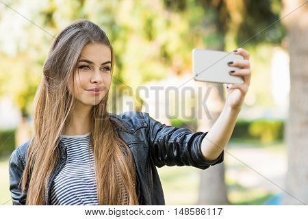 Beautiful blonde teenage girl taking a selfie on smart phone in park. Cute young woman with long blonde hair, smiling, taking a photo of herself on cellphone. No retouch, natural light.