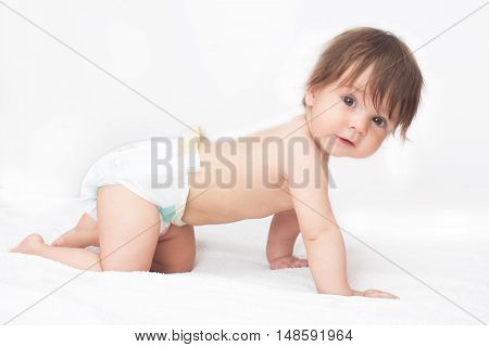 Bright picture of crawling baby girl in diaper.