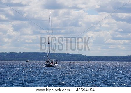 HARBOR SPRINGS, MICHIGAN / UNITED STATES - AUGUST 1, 2016: The sailboat Evolution leaves the Harbor Springs Municipal Marina.