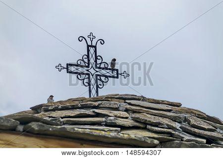 Giginski monastery, Bulgaria - June 25, 2016:  Stone slate-roof of old medieval church with cross in restored Montenegrin or Giginski monastery  St. St. Cosmas and Damian, mountain  Kitka, Breznik, Pernik region, Bulgaria. Visit in the place circa June 20