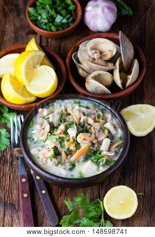 Latin American food. Seafood shellfish ceviche raw cold soup salad of seafood shellfish almejas, lemon, cilantro onion in clay bowl on wooden background. Traditional dish of Peru or Chile