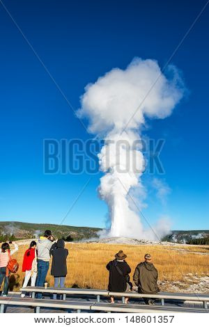 YELLOWSTONE NATIONAL PARK WY - SEPTEMBER 11: Crowd watches an eruption of Old Faithful in Yellowstone National Park on September 11 2015