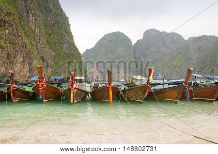 Boats lined up on Maya Bay located on Phi Phi Ley Island in Andaman Sea Thailand on Christmas day in the tropics.
