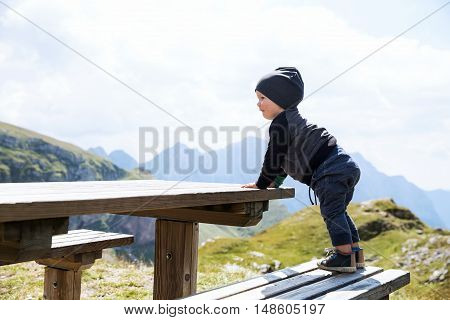 Cute baby child boy explore and looking at mountain view at the wood table. Picnic in the mountain. Family on a trekking day in the mountains. Mangart Julian Alps National Park in Slovenia Europe.