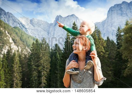 Happy mother and her child looking forward and pointing to sky. Family on trekking day in the mountains. Mangart Julian Alps National Park Slovenia Europe. Travel Explore Family Future Concept