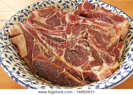Raw lamb chops cuts of mutton marinating in bowl poster