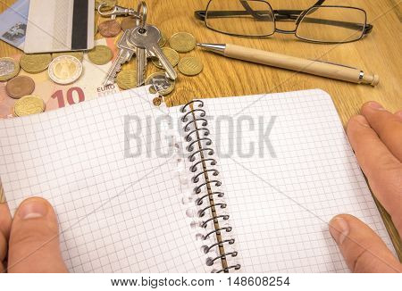 Blank sheet torn from a spiral notebook - Conceptual image with a man's hand tearing a blank page from a spiral math notebook money keys and credit cards in the background.