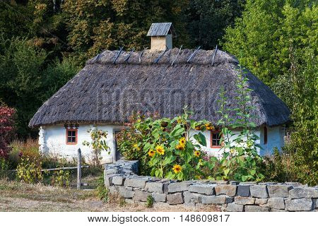Retro ukrainian cottage with thatched roof in Pirogovo village Kiev region Ukraine.