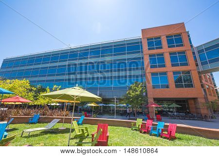 Mountain View, CA, USA - August 15, 2016: dining and relaxing area with colorful parasols and deck chairs for sunbathing for Google employees at Google's headquarters or Googleplex.