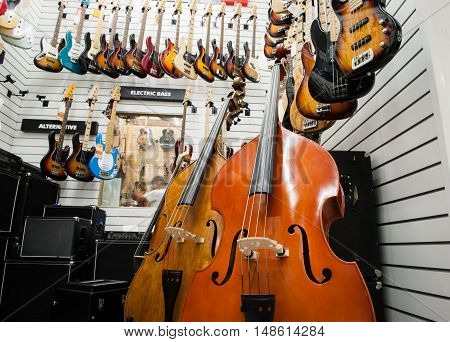 Rome Italy. September 20th 2016. Couple of double bass amplifier and many electric guitars hanging at the wall in stringed instrument store showroom
