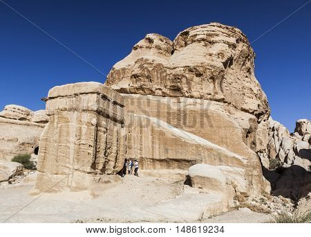 PETRA JORDAN - OCTOBER 29 2014: Unidentified tourists near one of the Djinn Blocks - the monuments that served as tombs and memorials to dead.