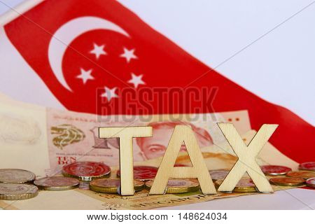 Tax sign with Singaporean notes, coins and flag.