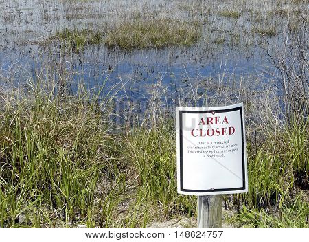 Conservation sign prohibits entry to an environmentally sensitive area where birds nest in the spring at St. Andrews State Park, Panama City, Florida.