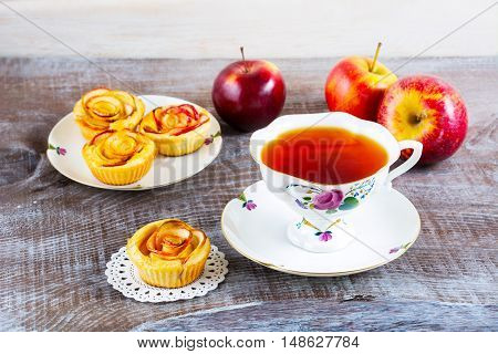 Cup of tea and small apple roses shaped pies. Sweet apple dessert pie. Homemade apple rose pastry. Breakfast tea with sweet apple pastry