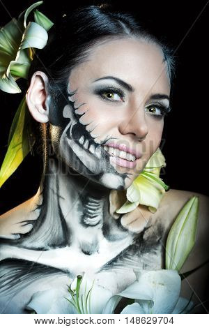 Young attractive girl with creative make-up for Halloween. Mysterious and frightening image of lilies. Witchcraft. Funk.