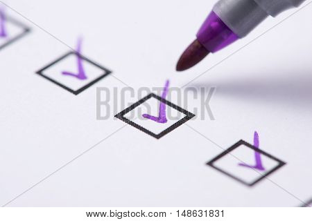 Checkbox with purple tick. Close-up of pupple pen over filled checkboxes in form