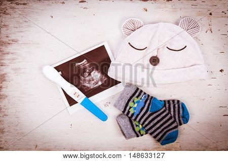 ultrasound with pregnancy test on wooden background