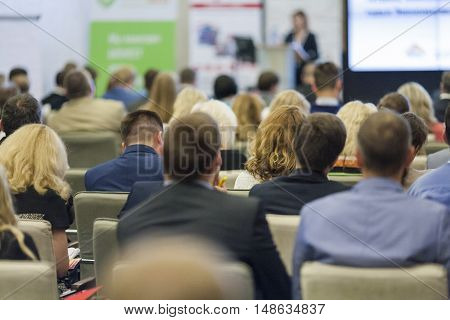 Professional Female Host Speaking in Front of the Audience During Business Conference.Horizontal Image Composition