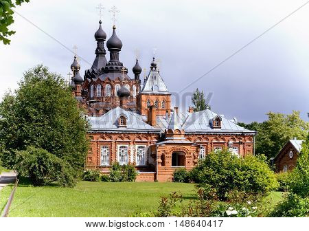 A beautiful Orthodox temple located on a hill surrounded by flowers and plants: arborvitae blue spruce shrubs. poster