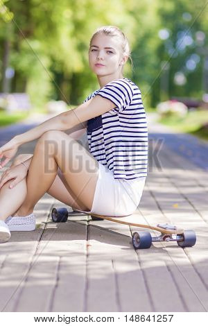 Teenagers Lifestyle Concepts and Ideas. Blond Caucasian Girl Posing With Longboard in Park Outdoors. Vertical Shot