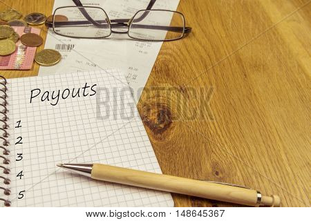 Empty payouts list on a notebook page - Financial concept with an empty payouts list written in a spiral notebook surrounded by money bills and a pair of glasses.