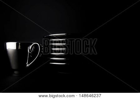 Rich black coffee. A single silver espresso cup by a stack of saucers isolated against a black background. The whole image is dark and luxurious reflecting the nature of a rich coffee.