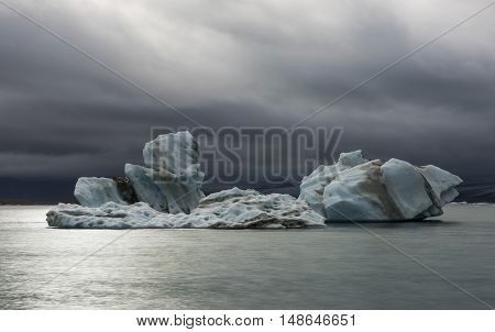 Ice block and dark clouds at the lake of Jokulsarlon glacier lagoon in the Vatnajokull National Park Iceland.