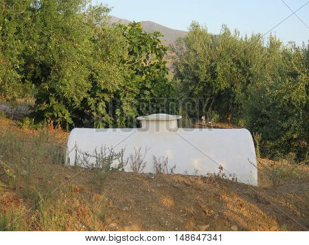 Half burried water storage tank in Andalusian countryside