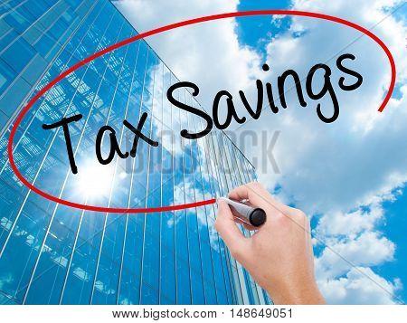 Man Hand Writing Tax Savings With Black Marker On Visual Screen