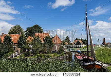 Enkhuizen The Netherlands - August 9 2016: Zuiderzee Museum Enkhuizen with old fisherman house fishing boat and small town in The Netherlands.