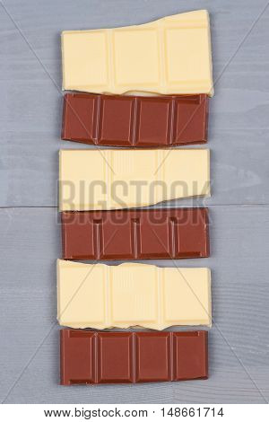 White and milk chocolate bars on natural grey wood background.