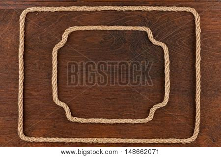 Two frame made of rope lies on a background of a wooden surface with place for your text