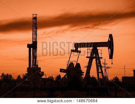 Oil rig and derrick silhouette during sunset in the oilfield. Oil and gas concept. Toned.
