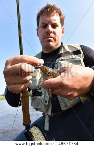 Closeup of brown trout being caught in river