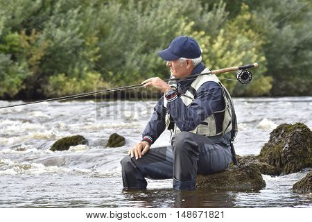 Fly-fisherman waiting with fishing pole on shoulder