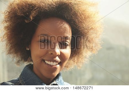 Outdoor Portrait Of Young Stylish Dark-skinned Female With Curly Hair Wearing Denim Jacket, Smiling,