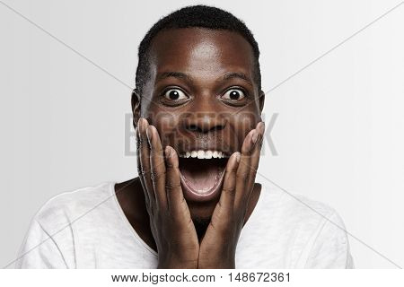 Shocked African Student Or Employee Looking At Camera In Full Disbelief, Hands On Cheeks, Mouth Wide