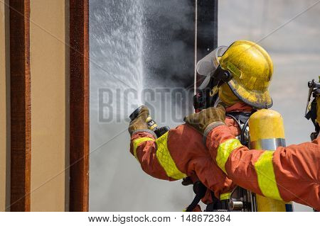 2 firefighter spraying practice at  model house in training course