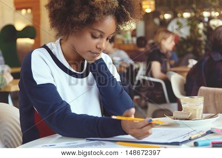 People and technology. Concentrated dark-skinned female freelancer working on touch pad writing out something in sheet of paper. Black student girl in casual top doing home task using modern gadget