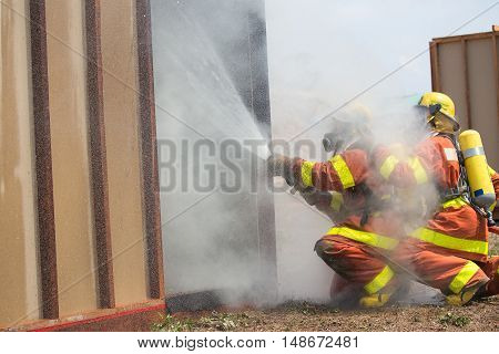 firefighter in fire protection suit spraying watersurround with smoke and drizzle in training