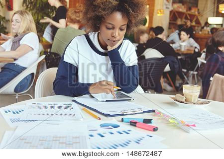 Young African Woman Entrepreneur With Serious Concentrated Expression Sitting At Coworking Cafe With